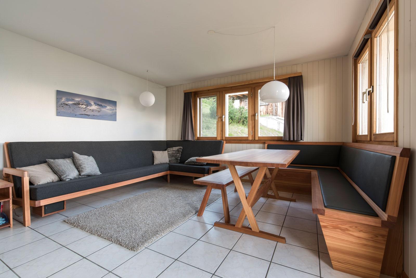 Stube mit Tisch, Bank und Sofa in Lärche